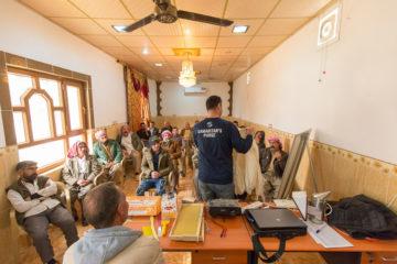 A Samaritan's Purse staff member teaches proper handling and honey harvesting techniques to bee program recipients.
