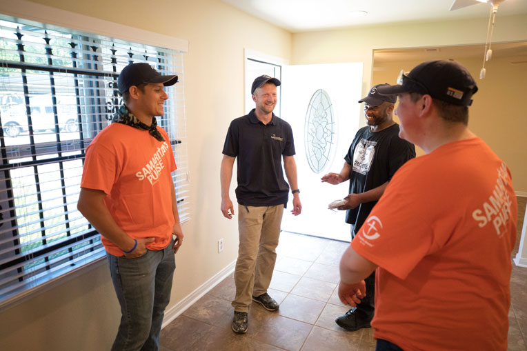 Carlin Toews, Samaritan's Purse construction supervisor, and our volunteers walk with Rodney through his new home.