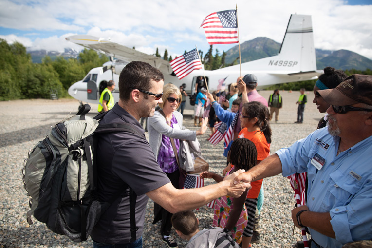 Marine Staff Sergeant Chris Stanton and his wife Crissy are greeted by children in the local community and by Samaritan Lodge staff and volunteers.