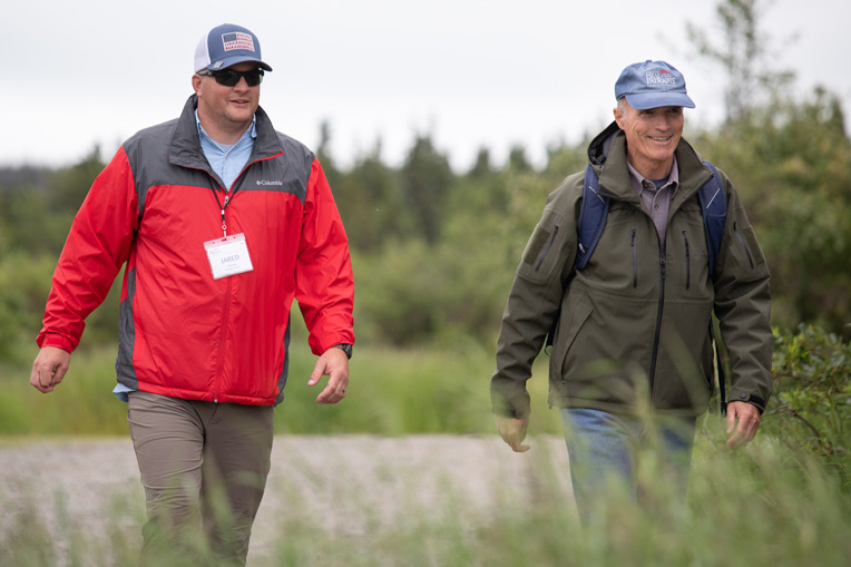 Army Staff Sergeant Jared Stacey walks to a bear viewing location with Retired Marine Brigadier General Jim Walker, Executive Director of Operation Heal Our Patriots.