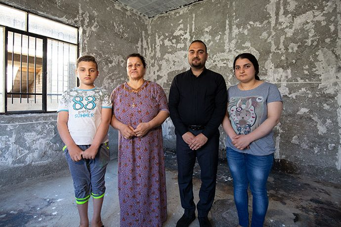 "Diana (second from left) and her children stand in their home that was burned by ISIS. Atheer, her eldest son, said, ""I am thankful that Samaritan's Purse is here."""