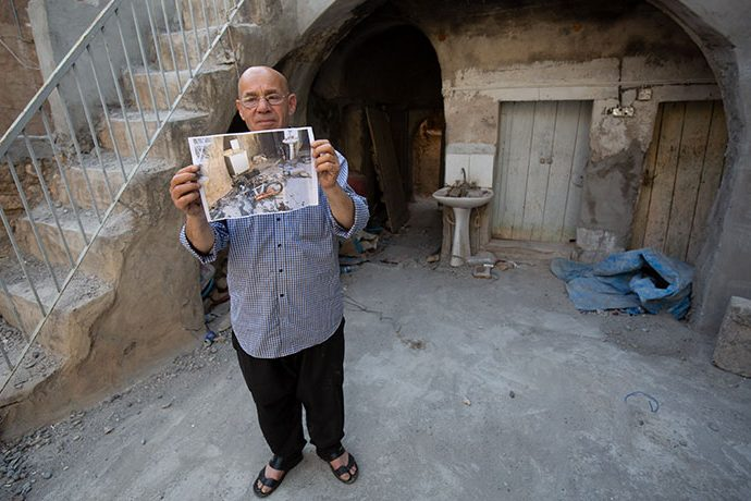 Yohannan displays a photo of what his home looked like when he first returned after his town was liberated from ISIS. Samaritan's Purse is repairing his home.