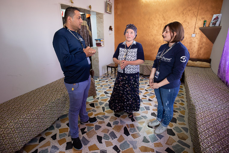 Anka and the Samaritan's Purse staff pray together in her newly restored home.