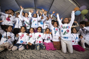After their graduation, child-friendly space graduates celebrate in the shirts they made in class.