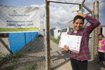 A graduate shows off his diploma from the CFS classes.