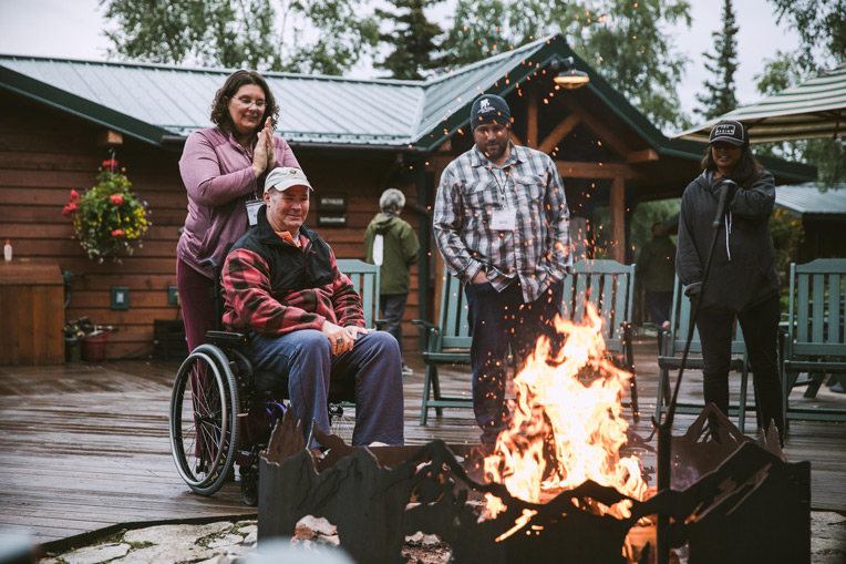 Nick and Bree, right, join Marine Master Gunnery Sergeant Marcus Fischer and his wife Brandi as the couples symbolically burn hurt and burdens in the fire at Samaritan Lodge.