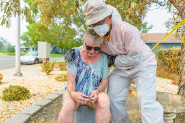 Volunteer Bert Won prays with homeowner Charlotte Bailey after finding cherished military dog tags from her deceased husband.
