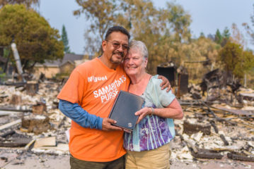Miguel Garcia presents a Bible to Charlotte Bailey after volunteers complete work at her house.
