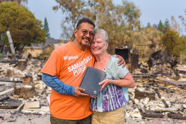 Site Team Leader Miguel Garcia presents Charlotte with a Billy Graham Bible signed by the volunteers who worked at her property.