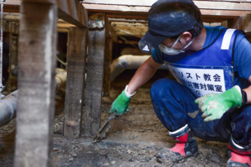 Volunteers are helping to clear mud from floor beams in a flood-stricken town in southern Japan.