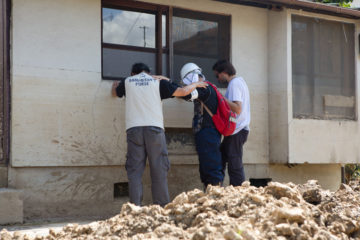 Members of our disaster response team pray with a worker helping clean up flooded homes in southern Japan.