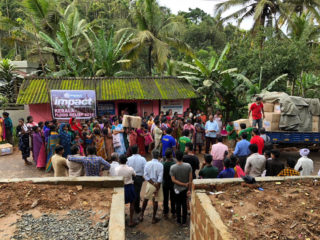 Families prepare to receive emergency relief supplies during a distribution in Northern Kerala.