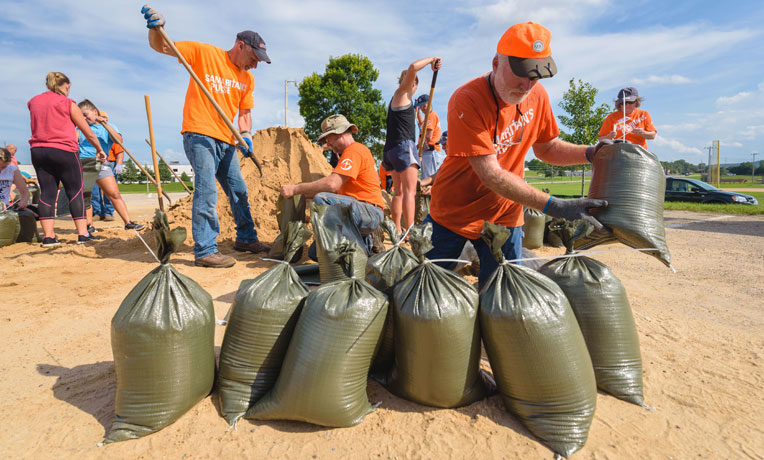 Samaritan's Purse volunteers work hard alongside community members to fill sandbags so that homeowners can use the bags to protect their property against rising floodwaters.