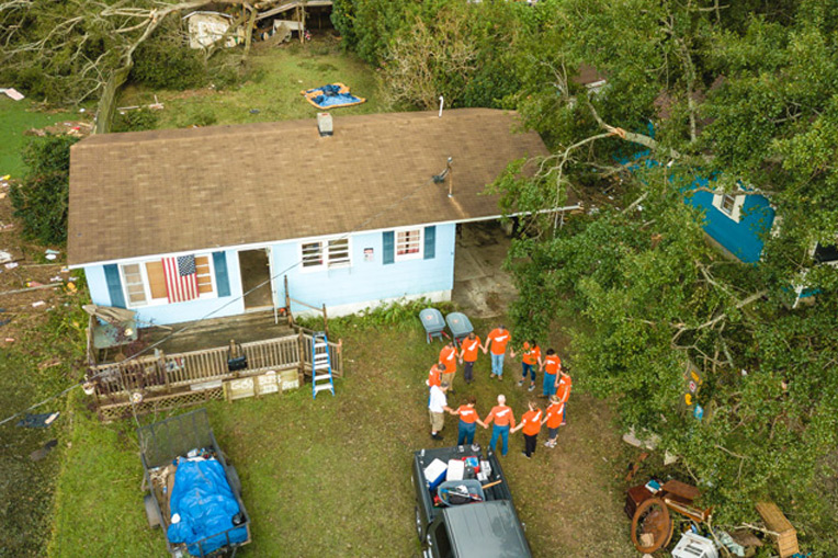 Volunteers pray at the home of Billy Connelly after completing work on his property.