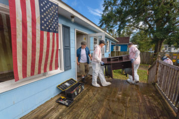 Volunteers help Billy Connelly remove valuables from his hurricane-damaged home.