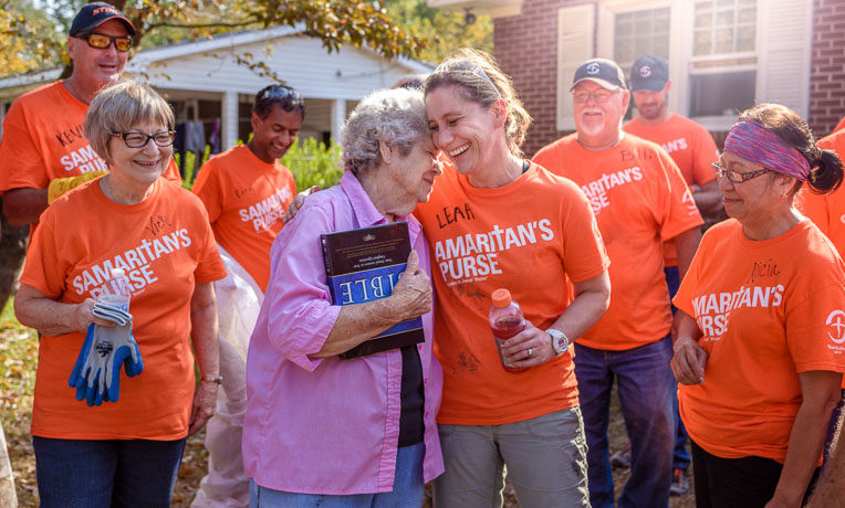 Samaritan's Purse volunteers present Love Whitfield with a Billy Graham Study Bible signed by the team after completing work at her home.