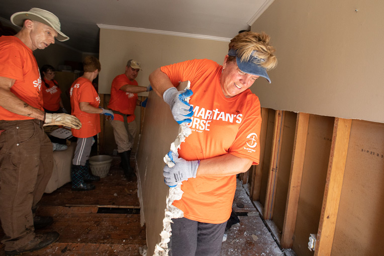 Volunteers clear wet walls and flooring from Mary Kerns' flooded home in Jacksonville.