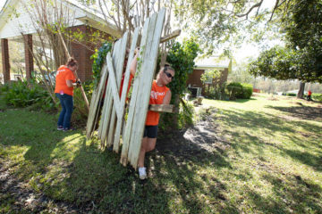 Volunteers remove damaged fencing and other debris from Carolyn Seeley's property.