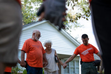 Volunteers pray with homeowner Carolyn Seeley before presenting her with a Billy Graham Study Bible signed by each team member.