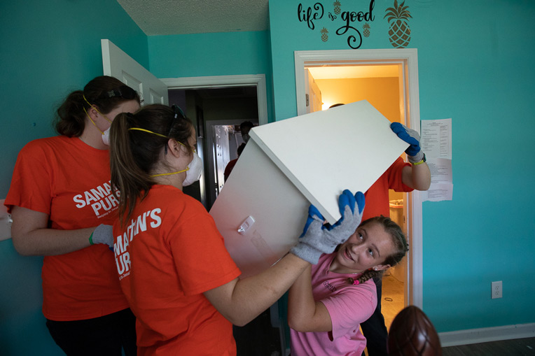 One homeowner's daughter, Mia, helped Liberty University students move furniture out of her rain-soaked room.