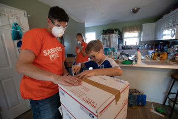 Briton's son, Massimo, helps a Liberty University volunteer pack up belongings.