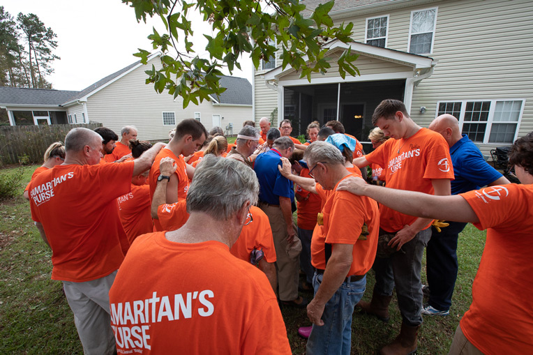 Volunteers and Billy Graham Rapid Response Team chaplains gather to pray over a homeowner in Wilmington.