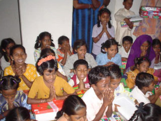Children in South Asia pray before opening the shoeboxes Raja and Ramya delivered to them from Christians around the world.