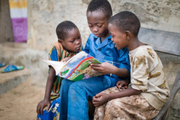 Kevin reads to siblings from The Greatest Journey booklet. The curriculum has helped introduce his family to God's Word.