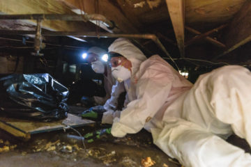 Samaritan's Purse volunteers remove debris from the sodden crawl space under Love Whitfield's home.