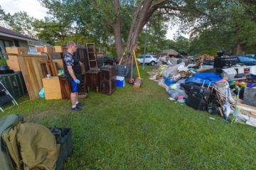 Jeremy Kulberg surveys piles of their belongings that are now rubbish to be carried away.