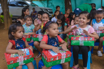Yariana's daughter (center) and niece (left) get ready to open their shoeboxes.