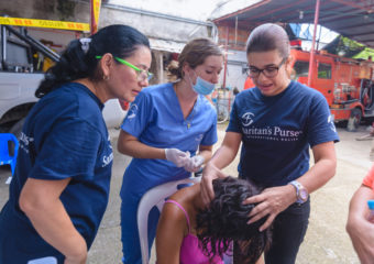 Doctor Maria De Los Angeles Sarmiento (right) and two nurses assess a woman's wounded head.