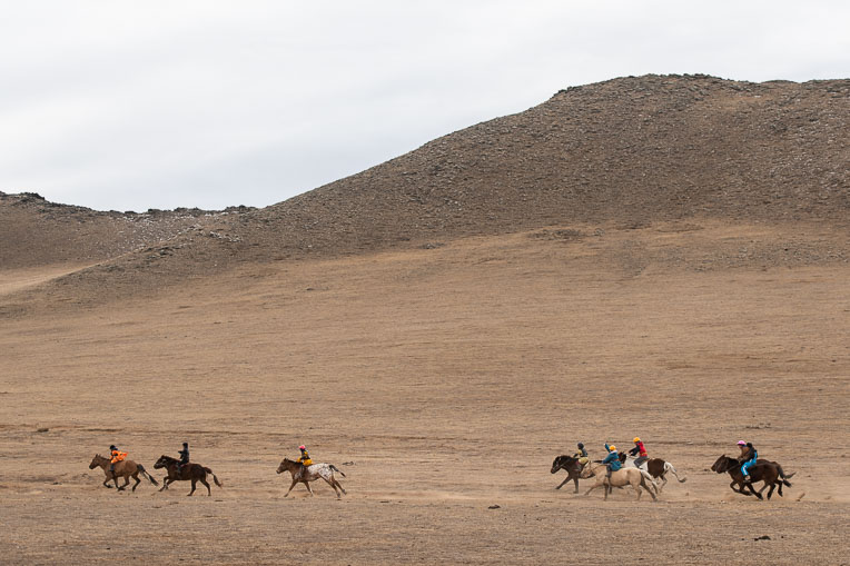 Mongolian horsemen race across the Mongolian grasslands in a furious chase for a finish line.