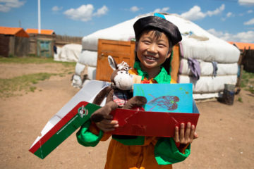 """A boy in Mongolia smiles after receiving his """"wow"""" toy and a personal note in the shoebox gift lovingly packed just for him."""