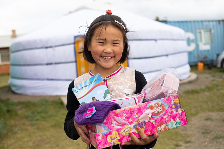 A young girl in Mongolia shows off the treasures she received in her shoebox, including a Gospel storybook in her language.