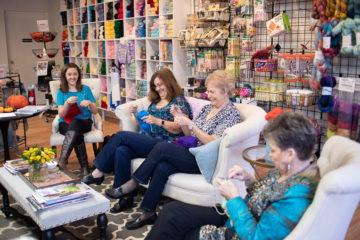 Sue (at right), Laquita, her neighbor Denise, and Alathia crochet at a local yarn store. Last year, they teamed up to help Alathia meet her 2,000-purse goal. This year, they are helping Alathia's and Laquita's church include crocheted purses in shoebox gifts.