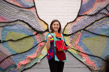 An artist at heart, Alathia displays an array of purses that she and her friends have made against the backdrop of a Fort Worth artist's depiction of a butterfly.
