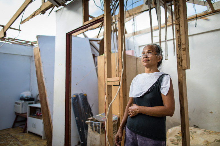 Sol Edad and her family hid under a table as Typhoon Yutu ripped the roof off of their Saipan home. They prayed that God would protect them from the storm; when the storm finally passed, all that remained of their home was the table under which they had been sheltered.