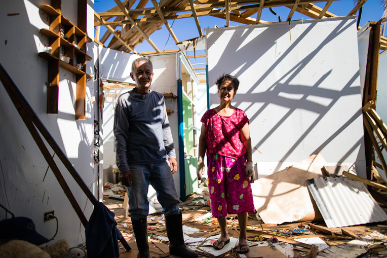 Rogelio and Evelyn stand in the top floor of their home. While the concrete structure remained upright, the high winds ripped off the roof and destroyed everything inside.