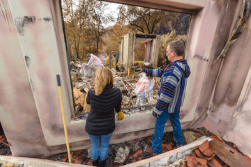 Marc and Janice Brusie survey their property through the window of one standing wall at their home.
