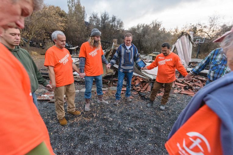 Volunteers pray with Marc Brusie during work at his Butte County home.