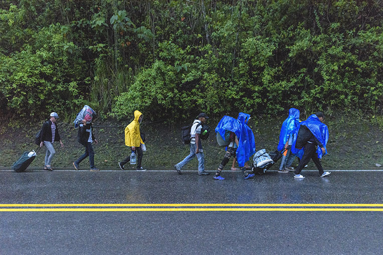 Venezuelan migrants walk in the rain with ponchos provided by Samaritan's Purse.