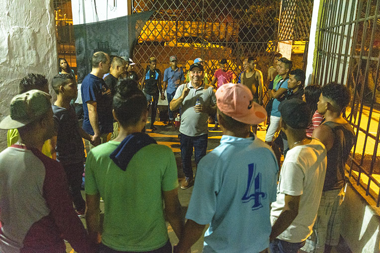 Pastor Jesus Paez preaches to Venezuelan migrants at night at the shelter.