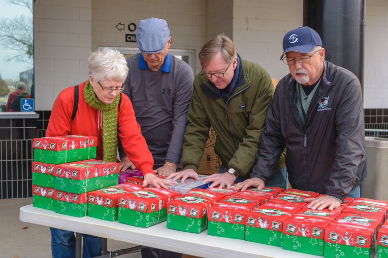 Steve Snow, area coordinator of Operation Christmas Child, gathers with local church leaders to pray over salvaged shoebox gifts.