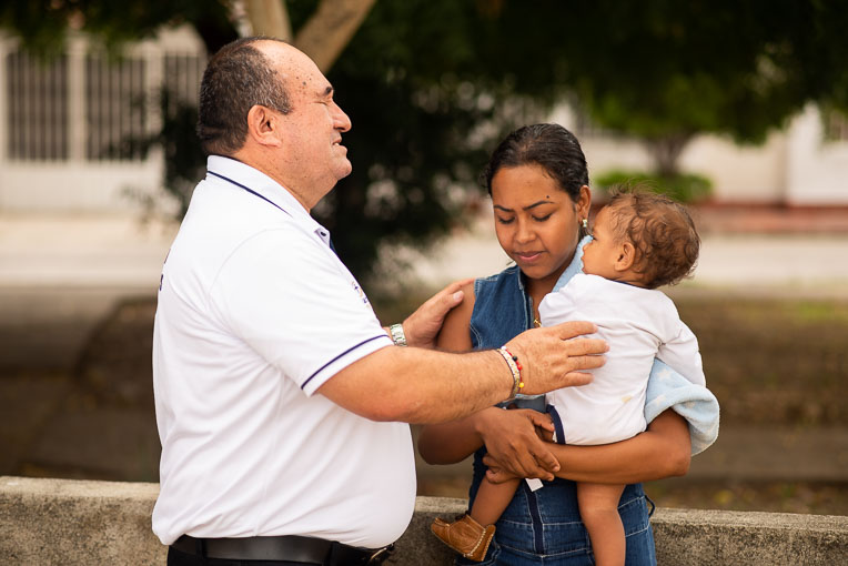 Jairo Antonio Garson Lopez, center coordinator, prays with Orangeles and her son.
