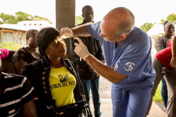 Agnus Weah receives an examination after cataract surgery restored her sight.