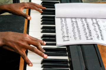 Playing the keyboard is an act of worship for Moise, who leads music during church worship services in his community.