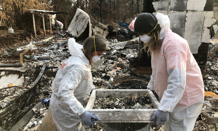 Volunteers sift through ashes at a home destroyed by wildfire in Paradise, California.