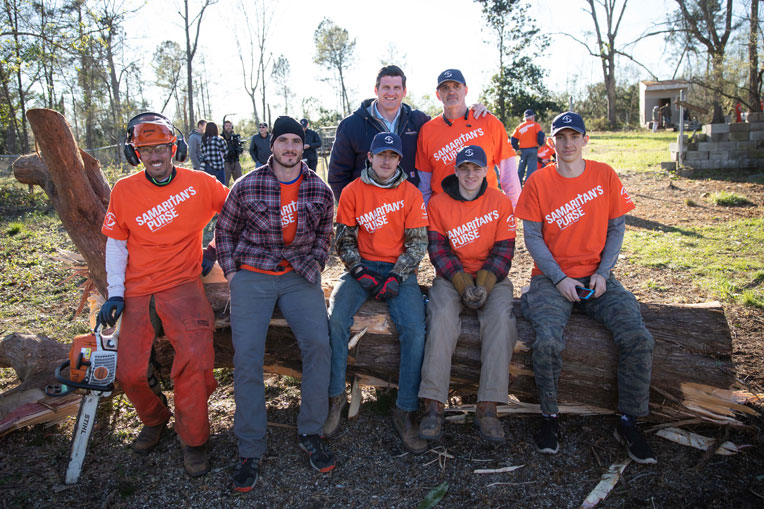 Edward Graham (at back center) stands with volunteers at an Alabama relief site.