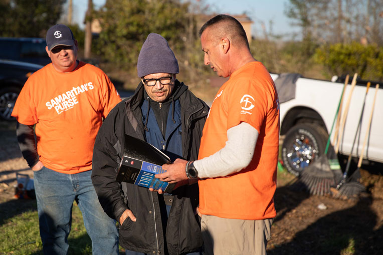 Our volunteers present a new Bible to a homeowner whose yard we helped clear.